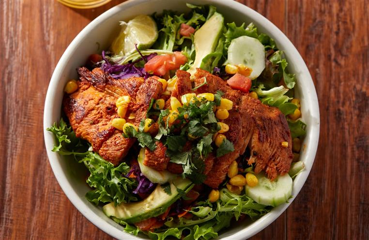 salad with mixed greens, tomatoes, cucumbers, avocado, grilled chicken and corn