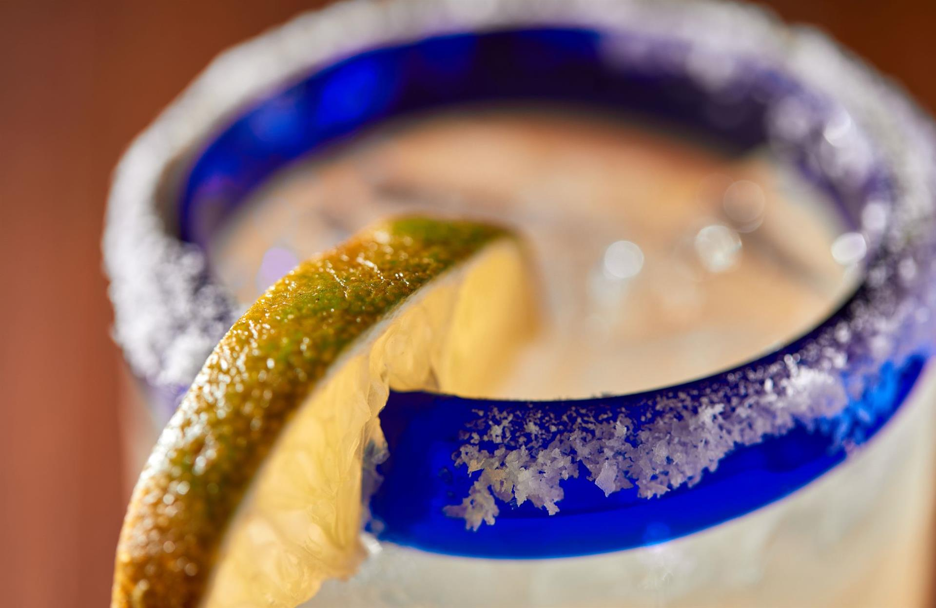 margarita on the rocks with a salt rim and a lime.