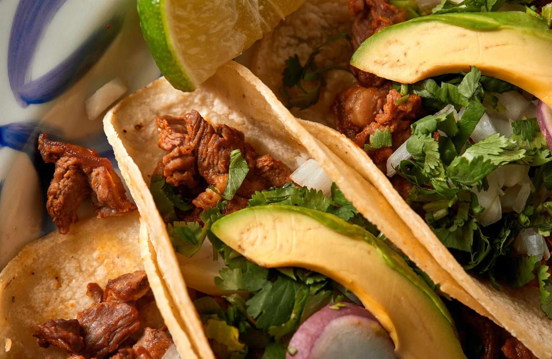plate with four soft tacos stuffed with meat, chopped onion, cilantro and avocado.