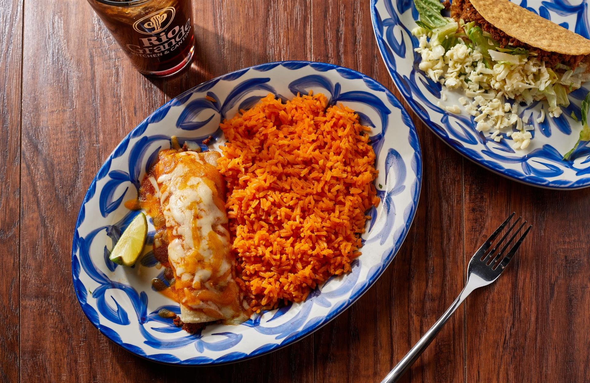 enchilada topped with sauce and melted cheese with spanish rice on the side.