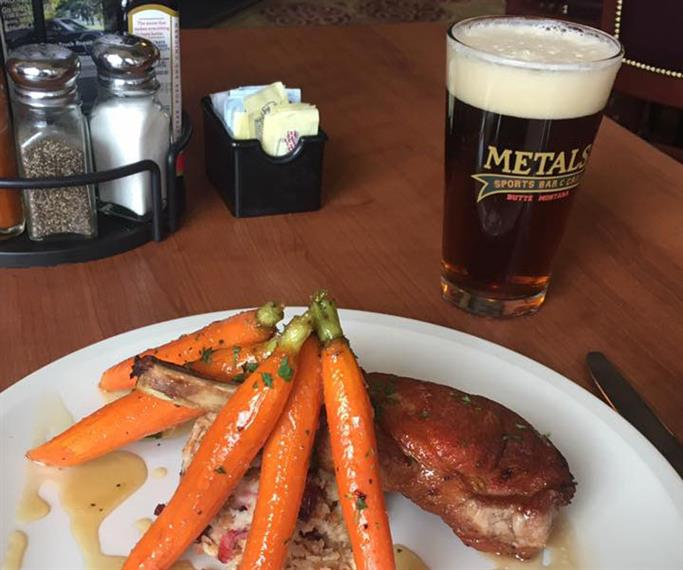 Roasted chicken topped with a gravy and roasted carrots
