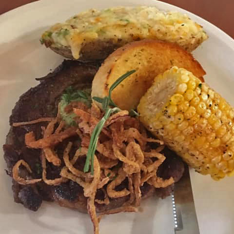 Steak topped with fried onions, garlic bread, a baked potato, and corn on the cob