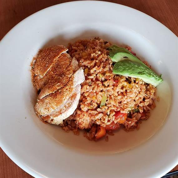 Chicken tenders over rice with cherry tomatoes and avocado