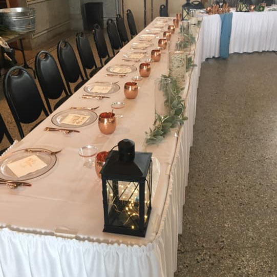 long table setup for a party with place settings and decorations