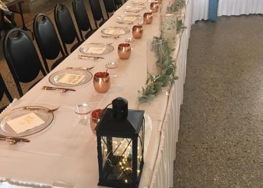 A long table and chairs set with linens and lantern centerpieces