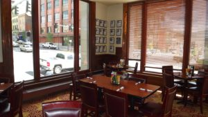 A private room with tables set in front of a large window overlooking the street