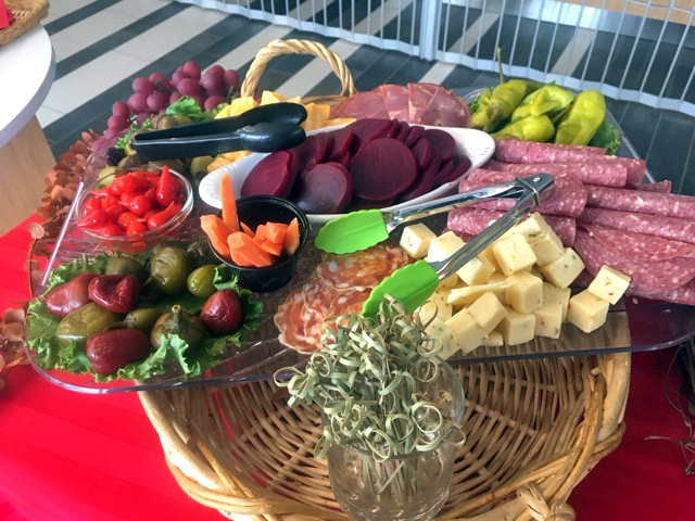 Charcuterie basket with various cold-cut meats, cheeses, and vegetables