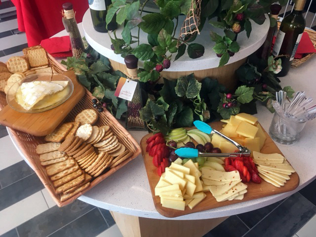 Charcuterie display which includes sliced cheeses, crackers, and hummus