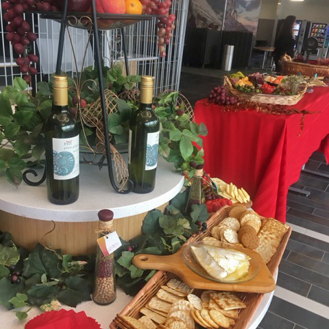 A wine, cheese, and crackers display table at a private event