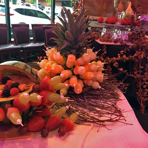 A display of melon balls, strawberries, and grapes on sticks, sticking out of a pineapple and watermelon.