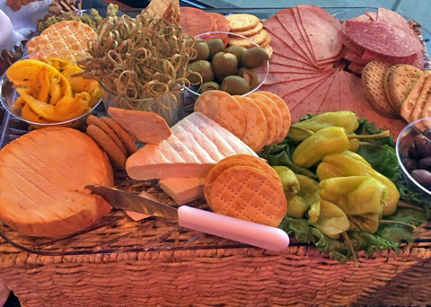 A charcutier basket with cheeses such as brie and cheddar, various sliced meats, and pepperoncini