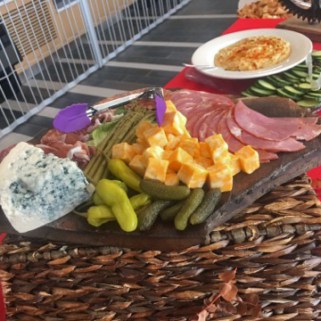 Sliced ham with cubes of cheddar cheese, pickles, and pepperoncini on a charcuterie board