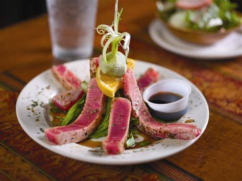 ahi tuna on a plate topped with garnish with a side of dipping sauce
