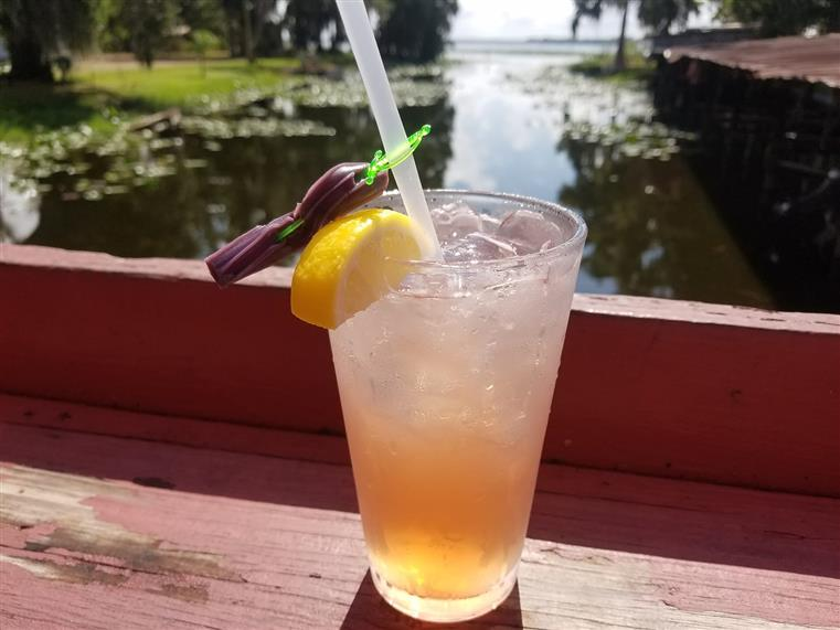 cocktail with a lemon wedge, sword and straw