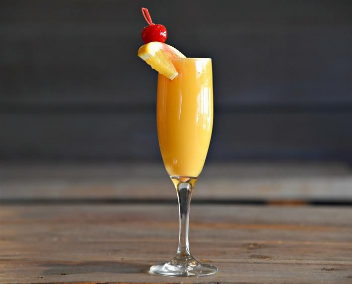 Mimosa topped with an orange and cherry