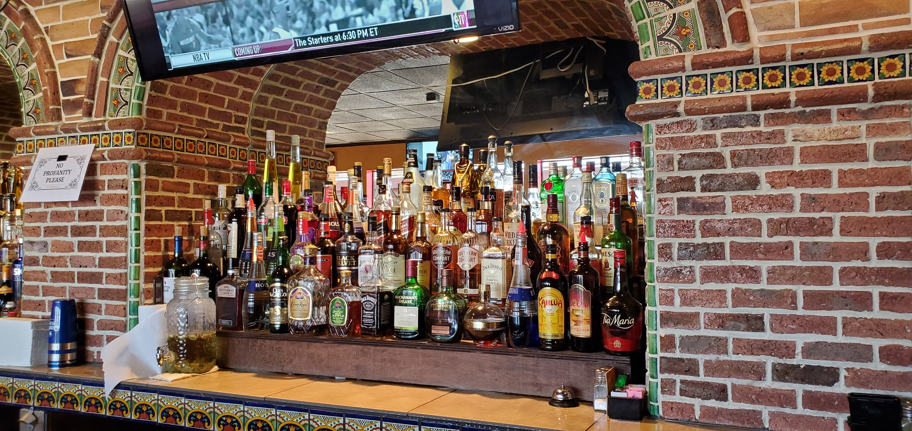shelves of liquor on the wall behind the bar.