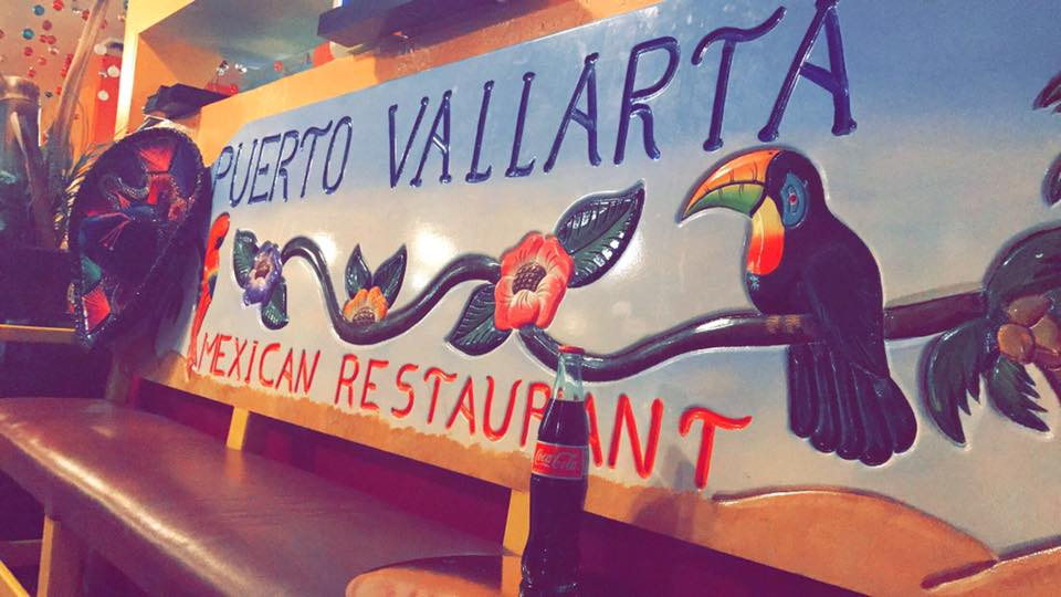 "Bench with painting of birds and flowers on it that says ""Puerto Vallarta Mexican Restaurant"""
