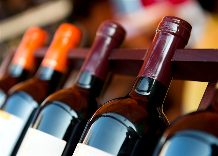 bottles of red wine lined up in a row on a wine rack