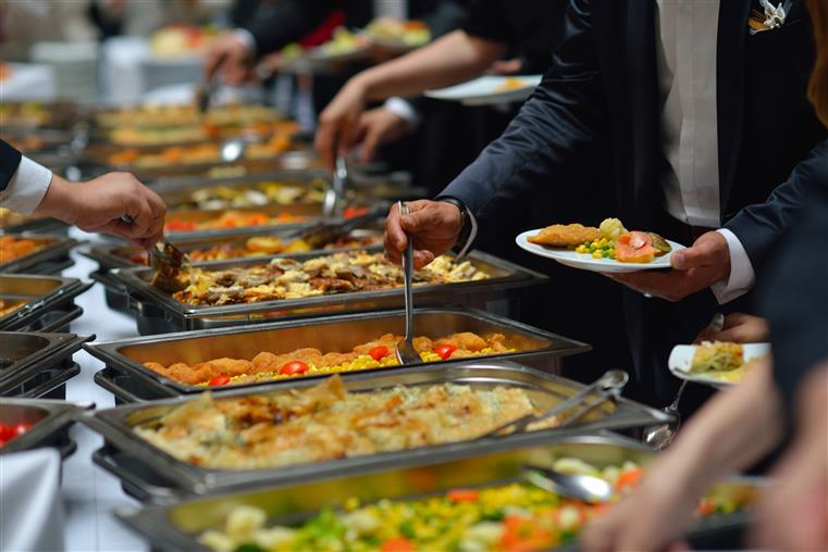 buffet with various trays of assorted dishes with people serving themselves