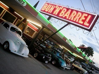 The Carhop lit up with neon lights at night and vintage cars parked in the carhop