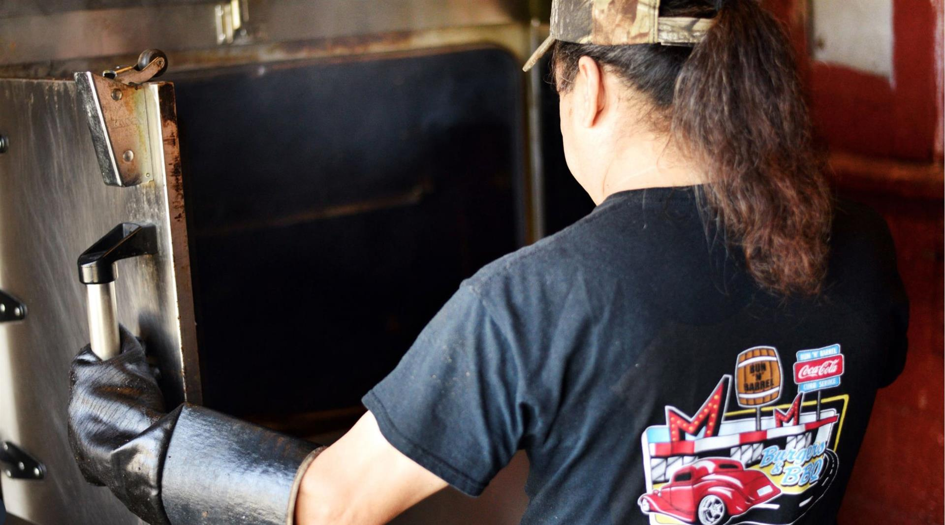 A staff member opening the oven in the BBQ pit kitchen