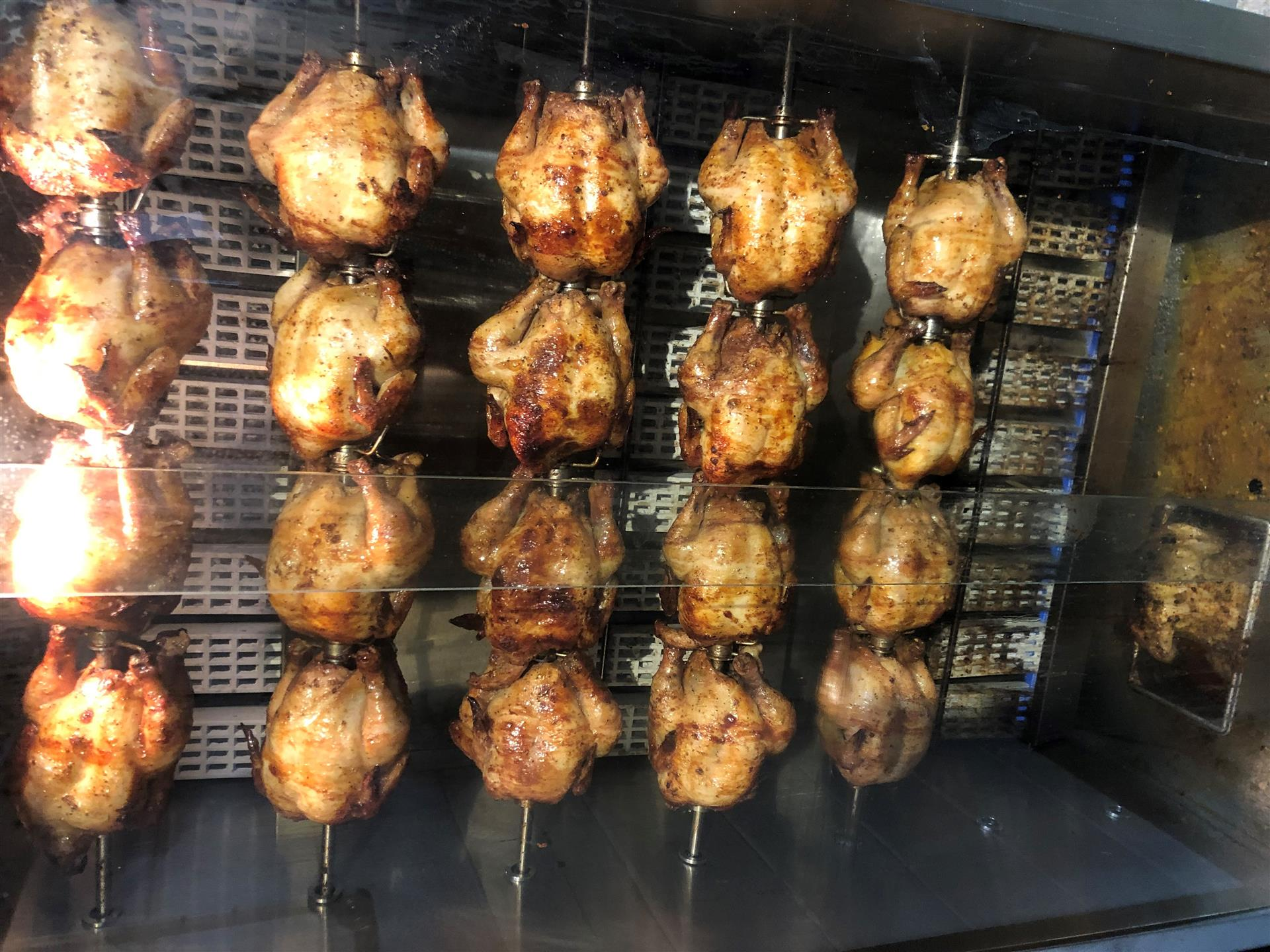 Chickens roasting in outdoor BBQ pit