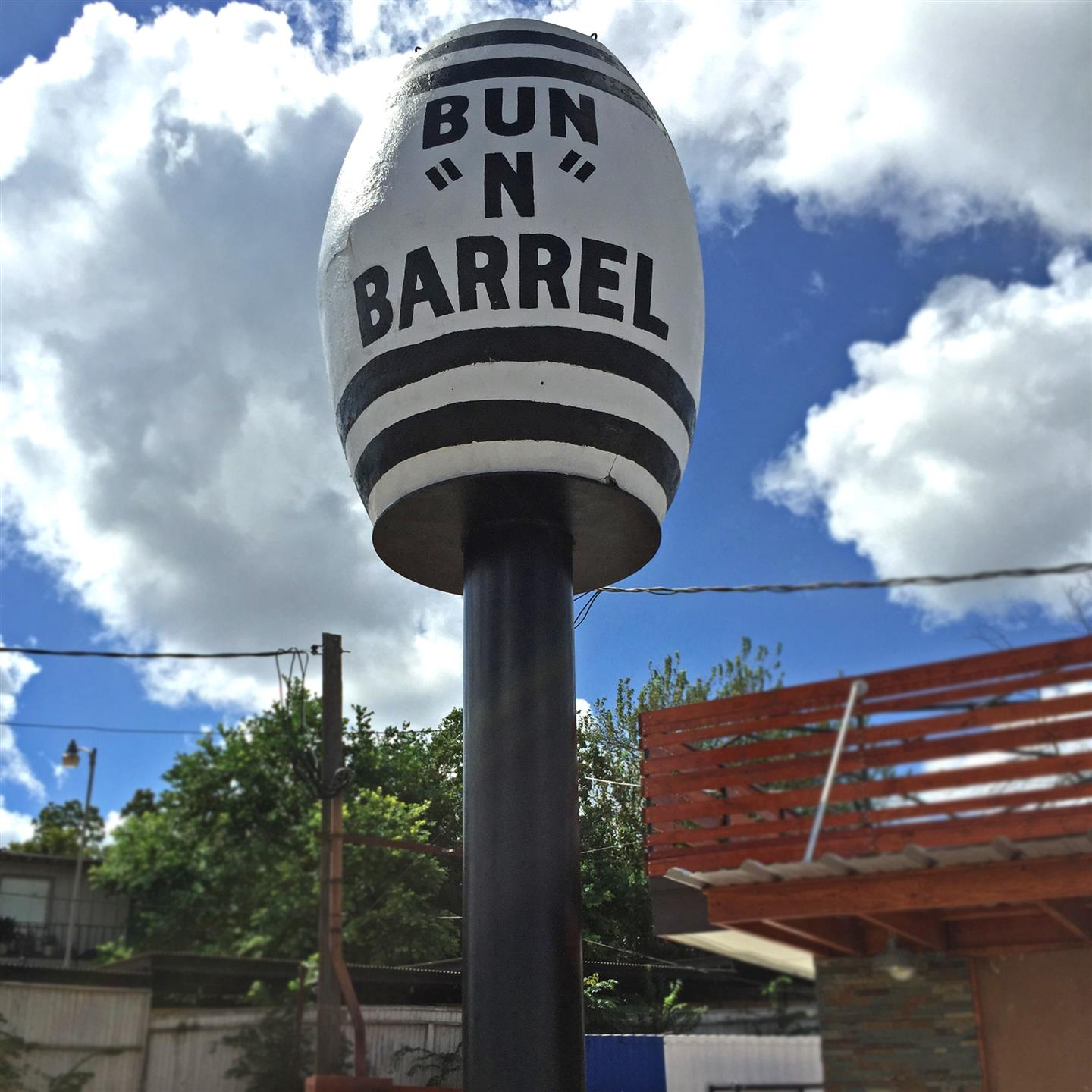 "A giant round statue that says ""Bun-N-Barrel"""