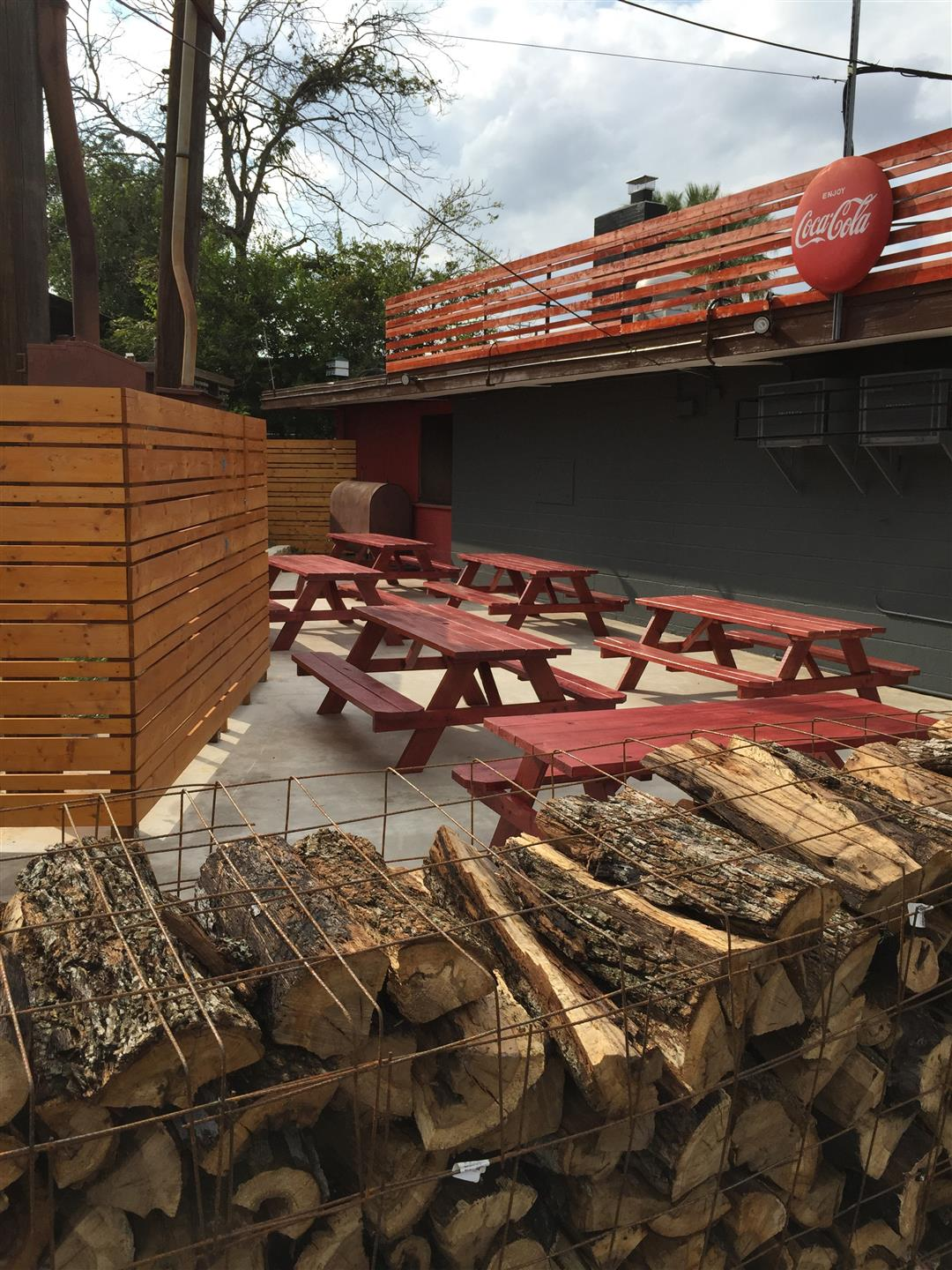 Outdoor seating area behind the BBQ pit with benches and stacks of firewood