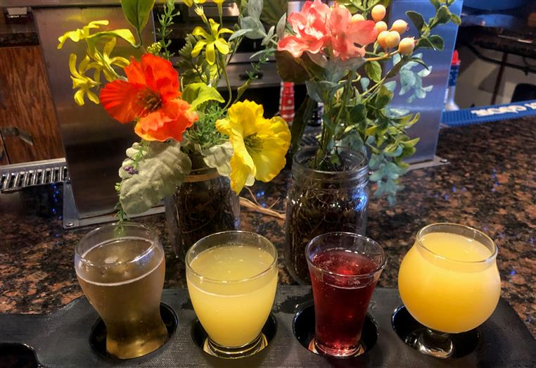 flight of assorted drinks with flowers behind it.