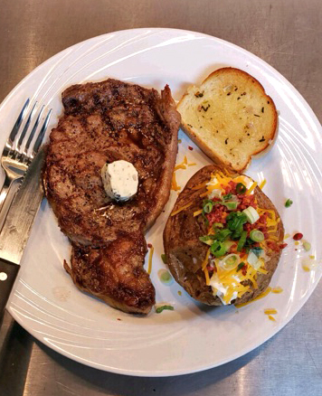 Steak with a loaded baked potato and garlic bread on the side