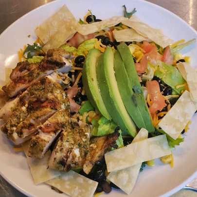 A Mexican style salad topped with grilled chicken, cheese, tortilla chips, black beans, corn, tomato, and avocado