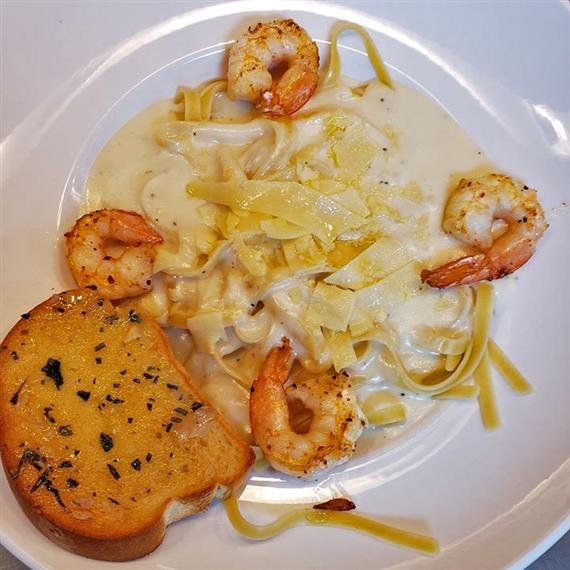 Linguine Alfredo with grilled shrimp and garlic bread on the side