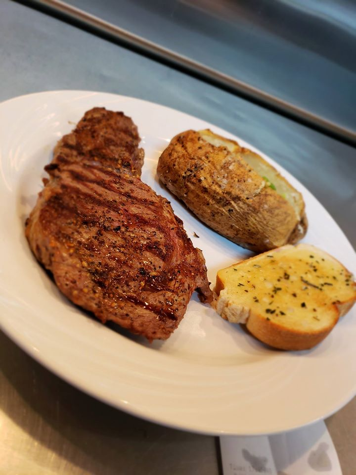 Steak topped with butter, with a side of a loaded baked potato and garlic bread