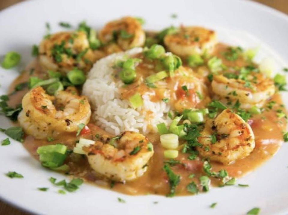A scoop of white rice topped with shrimp, brown sauce, and scallions