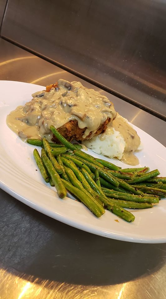 Fried chicken topped with mushroom gravy with a side of green beans