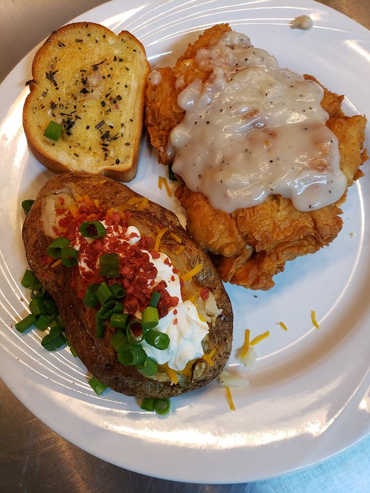 Chicken fried steak topped with gravy, with a side of garlic bread and a loaded baked potato