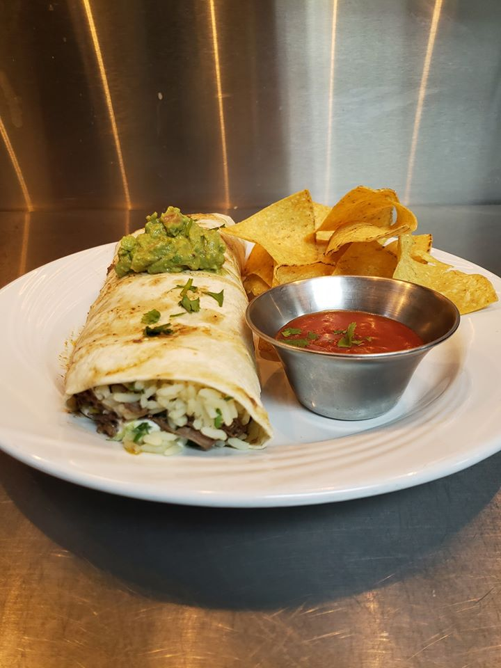 A rice and steak burrito topped with cilantro and a side of salsa with chips