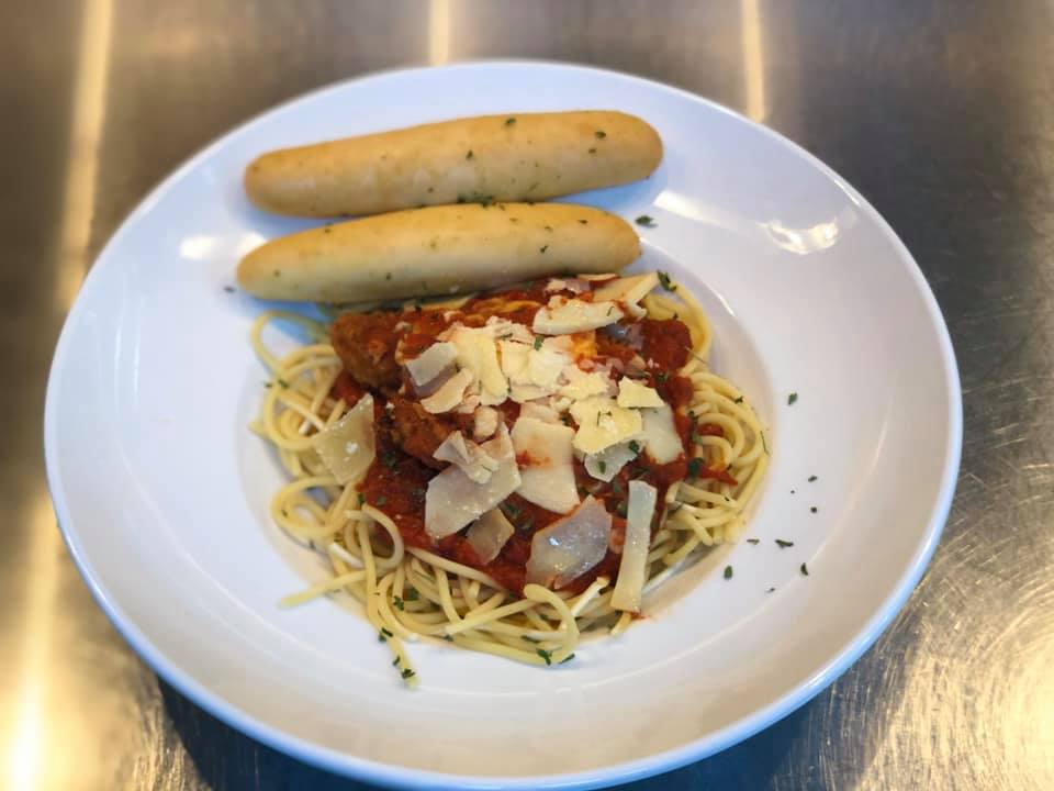 Spaghetti topped with tomato sauce, parmesan, and a side of garlic bread