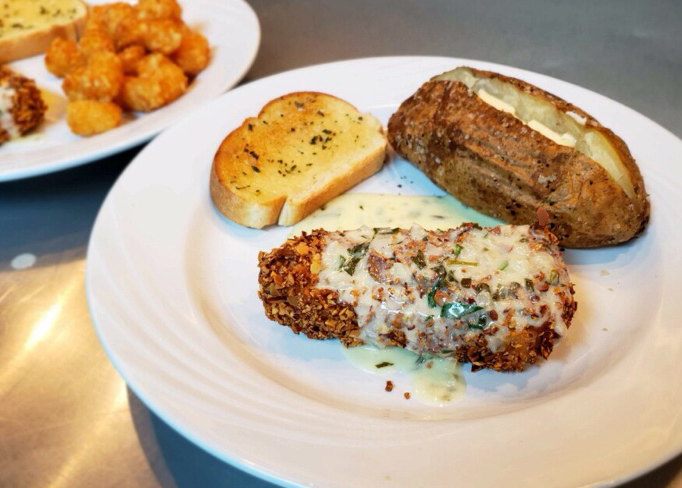 Chicken fried steak with a baked potato and a slice of garlic bread on the side