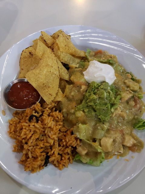 Tortilla chips with a Mexican burrito salad, including rice, guacamole, chicken, lettuce, and salsa
