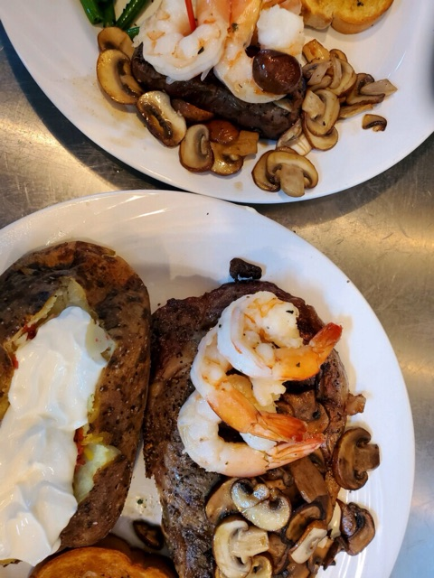 Steak topped with shrimp, mushroom, and a baked potato on the side