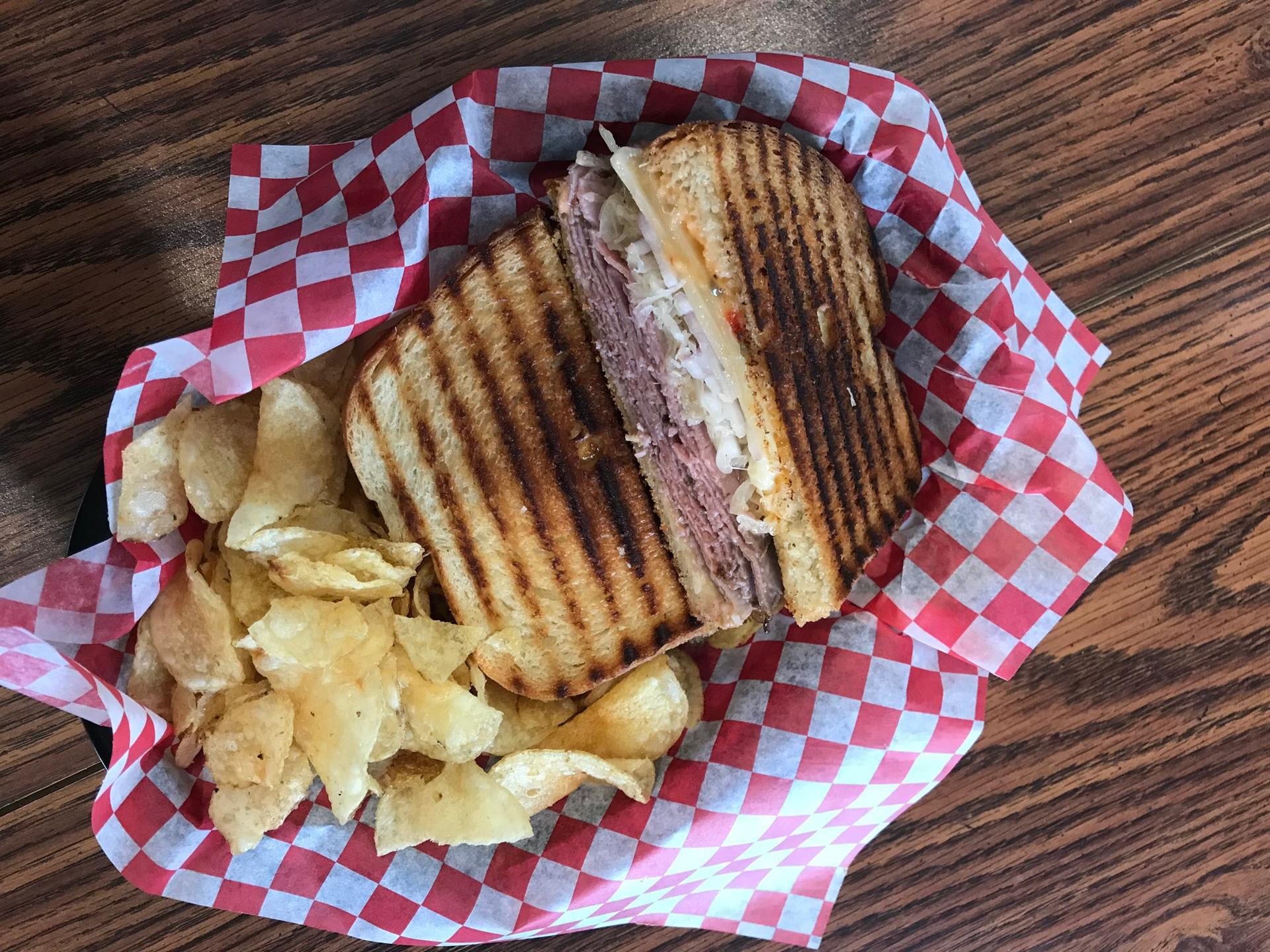grilled cheese with ham, in a basket with potato chips