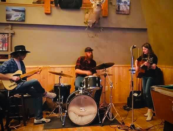 three piece band playing live music inside the restaurant