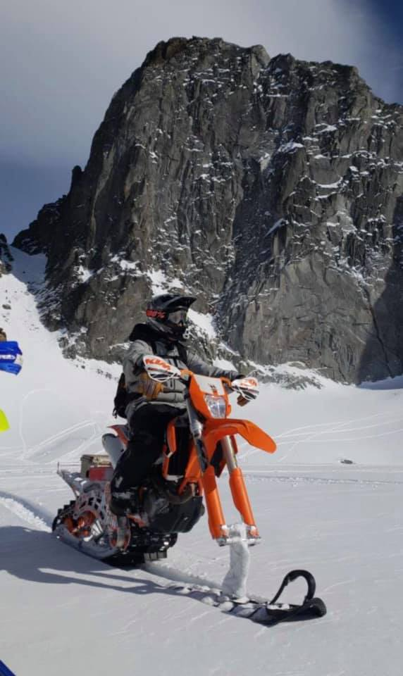 someone riding their dirtbike through the snow on the track