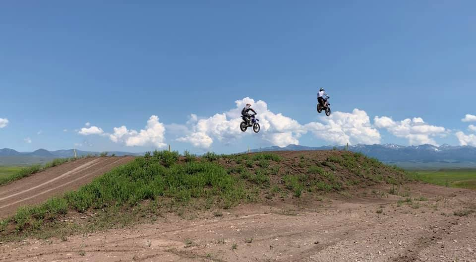 two people riding a dirt bike through the track