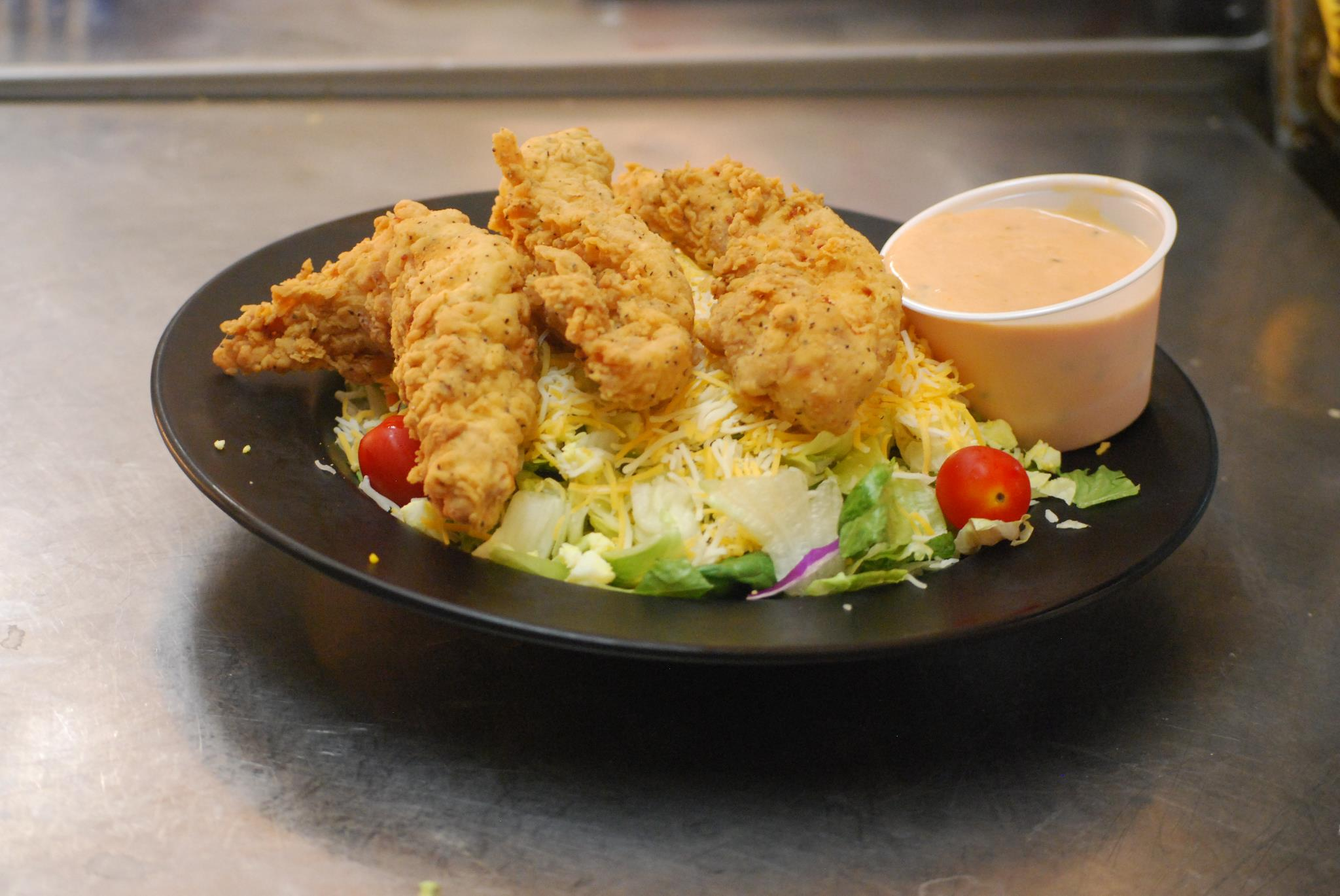 Crispy chicken tenders with dipping sauce placed on top of a salad in a bowl
