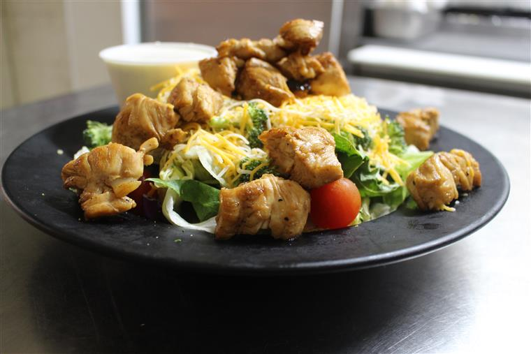 chicken salad with lettuce, tomatoes, cheese, croutons with a side of dressing