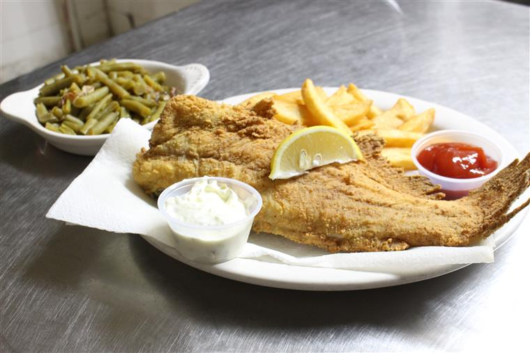 Fried fish and fries with a side of dipping sauces on a plate with a side of green beans