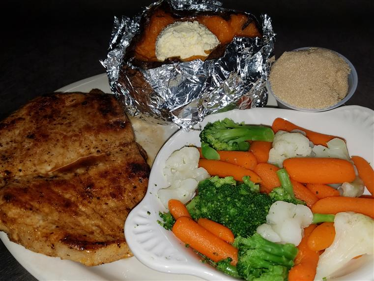 grilled porkchop with a plate of veggies and a baked sweet potato with a side of cinnamon butter