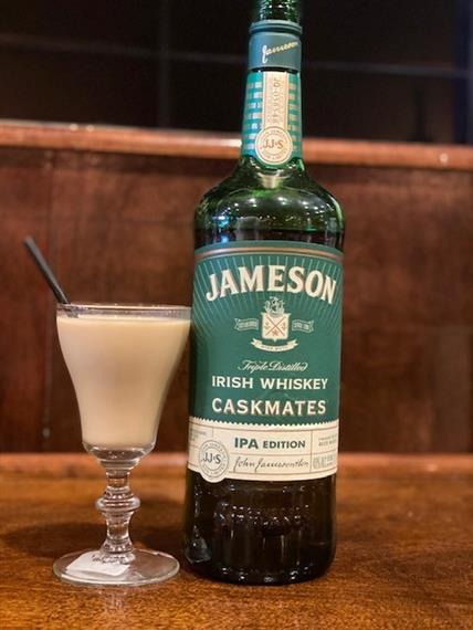 cup of irish coffee with a bottle of jameson whiskey